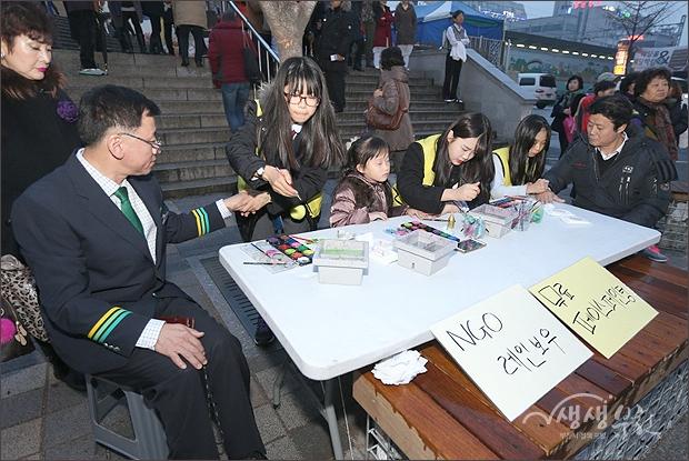 ▲ 자원봉사 나온 여학생들이 페이스페인팅을 그려주는 모습