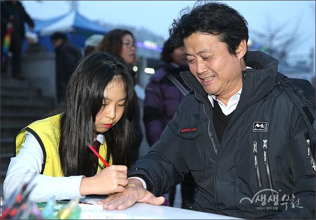 ▲ 김만수 시장의 손등에 정성껏 그림을 그리는 여학생