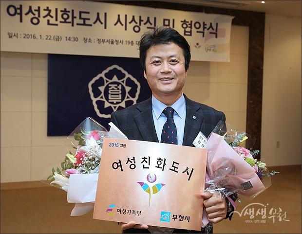 ▲ 여성친화도시 현판을 들어보이는 김만수시장.