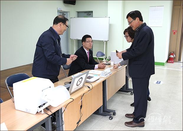 ▲ 본인임을 확인할 신분증을 제시하고 선거구 해당 선거구 관내와 관외지역으로 구분된 투표용지를 받는 시민.