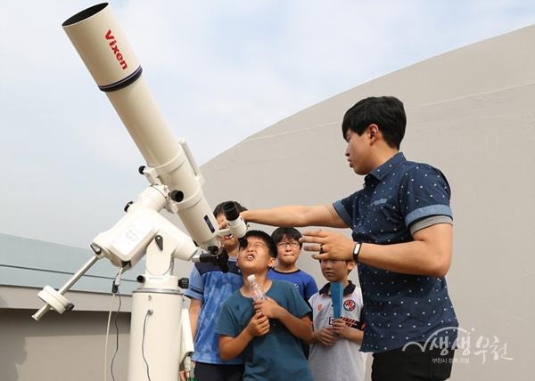 ▲ 관람객이 천체망원경을 들여다 보고 있다.