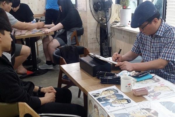 ▲ 정재훈 작가가 청소년들의 캐리커처를 그리고 있다.