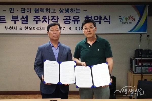 ▲ 양완식 부천시 공동주택과장(왼쪽)과 이윤홍 한오아파트 운영위원회장이 협약서를 보이고 있다.