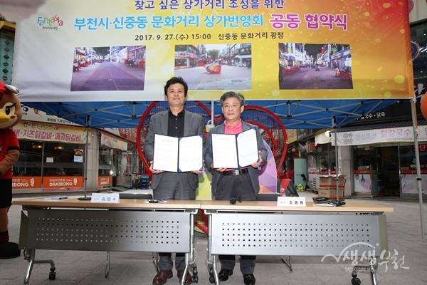 ▲ 김만수 부천시장(왼쪽)과 조종원 신중동문화거리 상가번영회장이 협약서를 들어보이고 있다.
