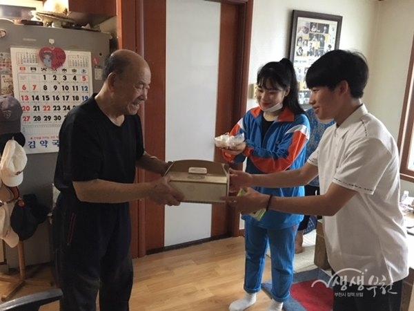 ▲ 정성을 다해 만든 떡케이크를 전달하고 있는 학생들