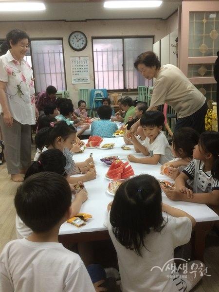 ▲ 비누공예 체험을 위해 경로당을 찾은 꿈별유치원 원아들이 할머니들이 준비해준 수박을 먹고 있다.