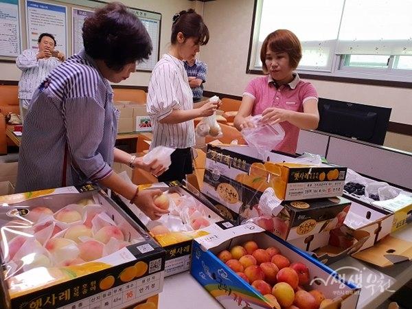 ▲ 과일 선물상자를 만들고 있는 상1동 복지협의체위원들