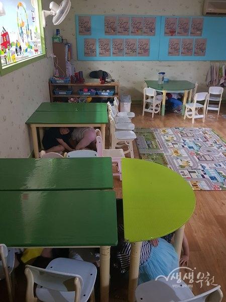 ▲ 괴안동 동산어린이집 아동들이 지진 경보에 책상밑으로 대피하고 있다.