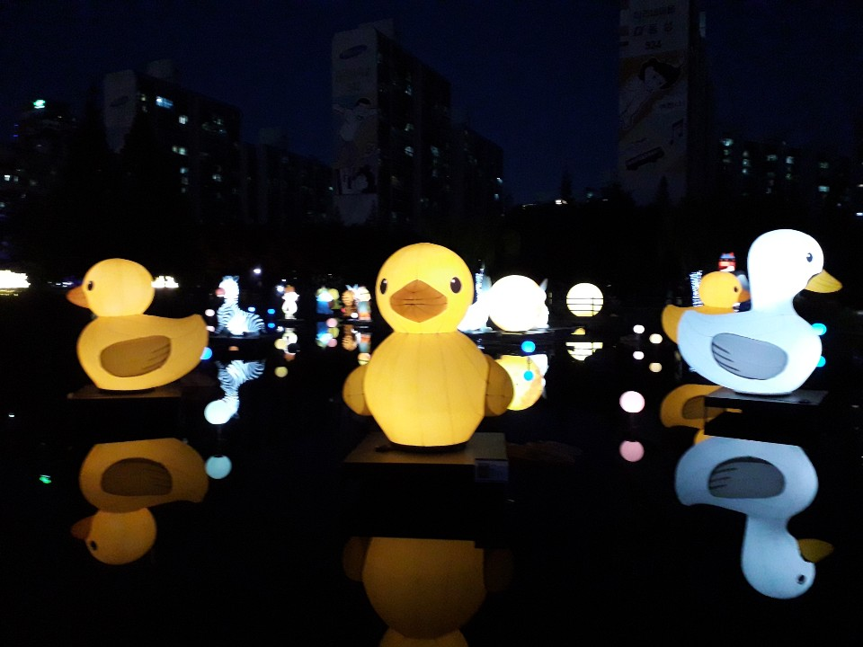 어두운 저녁, 공원 물가에 비친 등의 모습이 인상적이다.