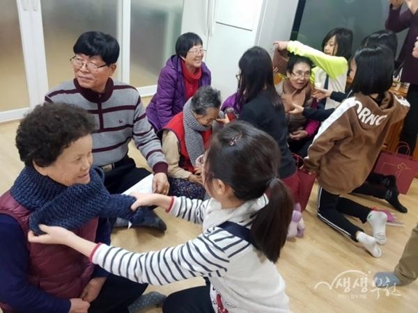 ▲ 도담지역아동센터 아동들이 직접 만든 목도리를 경로당 어르신들께 선물하고 있다.