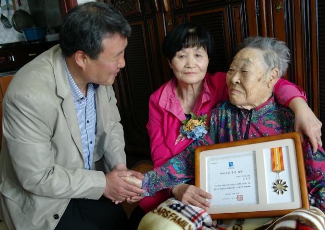 ▲ 100세 시어머니의 손을 잡고 격려를 하는 정영배 춘의동장
