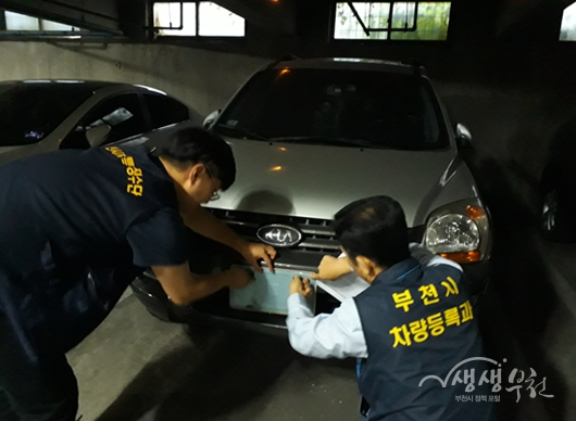 ▲ 부천시 단속반이 의무보험 미가입 차량 번호판을 영치하고 있다.