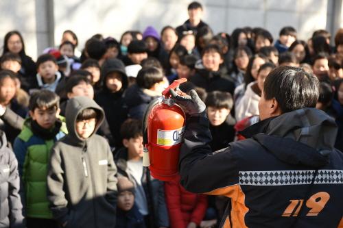 ▲ 소방대원이 야외로 대피한 학생들에게 소화기 사용 교육을 하고 있다.