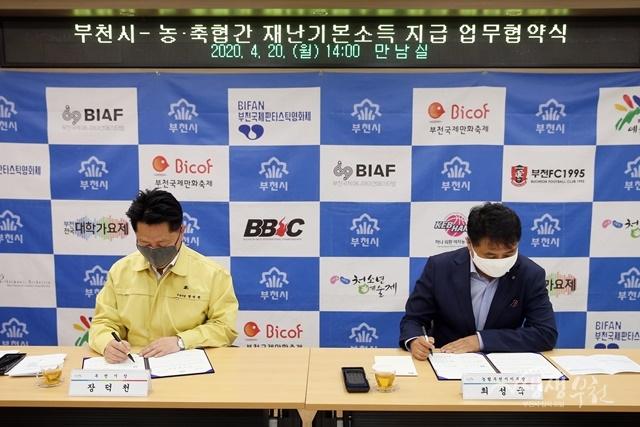 ▲ 장덕천 부천시장(왼쪽)과 최성국 농협부천시지부장(오른쪽)이 재난기본소득 신청 및 운영을 위한 업무 협약에 서명하고 있다
