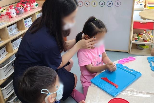 ▲ 부천시 어린이집 교사가 아이에게 붙이는 체온계를 붙이고 있다